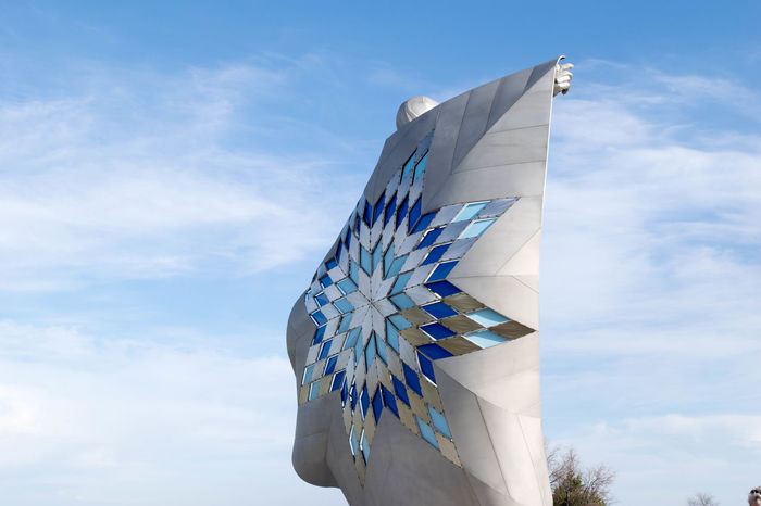 Dignity Native American Indian South Dakota Statue Art And Craft Blue Built Structure Chamberlain Cloud - Sky Creativity Day Environment Flag Low Angle View Native American Nature No People Outdoors Patriotism Pattern Shape Sky Sunlight White Color Wind