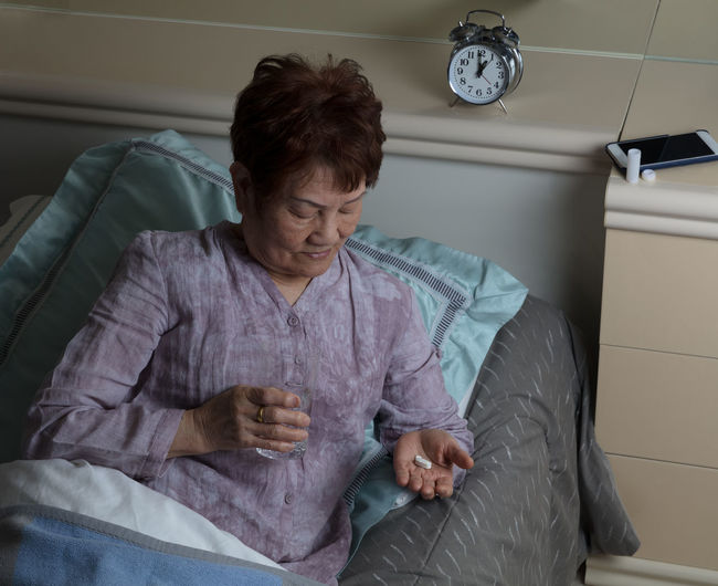 High Angle View Of Senior Woman Eating Medicine While Lying On Bed At Home