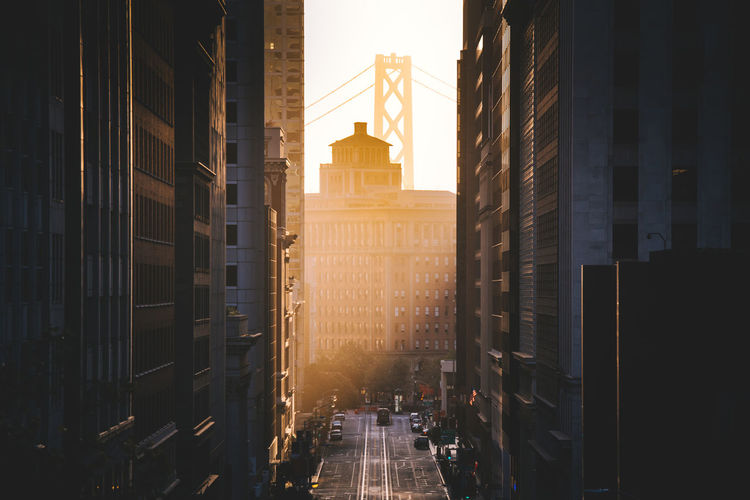 Road amidst buildings in city during sunrise