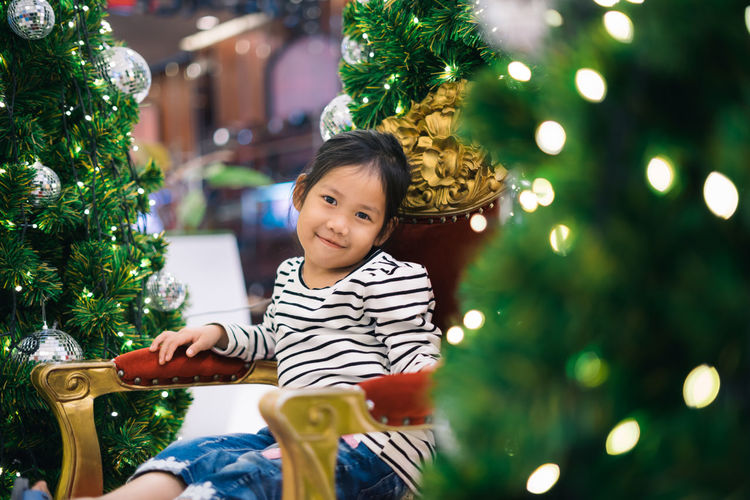 Portrait Of Cute Girl Sitting On Armchair Amidst Christmas Trees