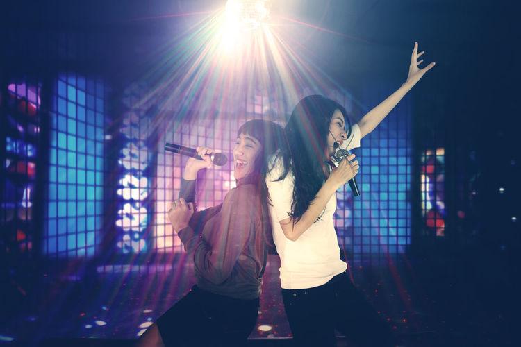 Friends dancing and singing in nightclub