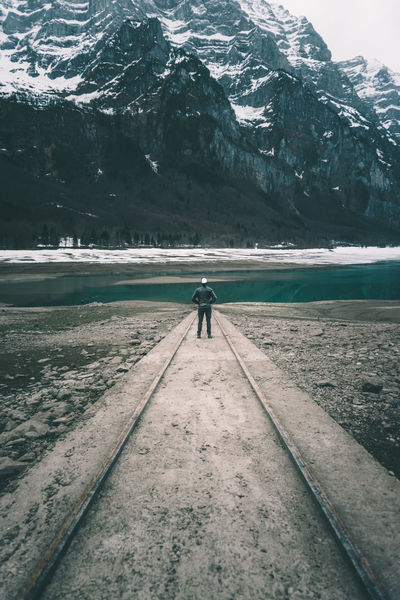 Man in leather jacket standing at mountain lake Alps Cloudy Focus Focus Point Klöntal Klöntalersee Landscape Leading Lines Lines Lonely Man Man Standing Mountain Lake Mountains Peaceful Schweiz Snow Suisse  Svizzera Swiss Swiss Alps Swiss Mountains Switzerland Thinking Tranquility
