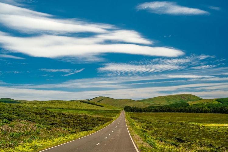 Surface level of road along landscape against sky