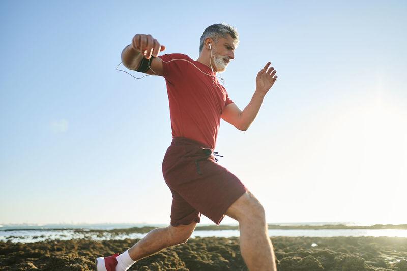 Full length of senior man on beach against sky