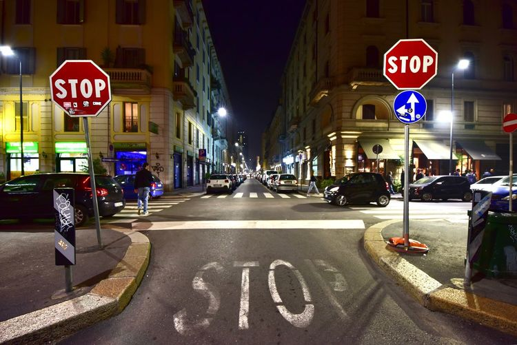 Sign City Communication Text Architecture Road Sign Road Marking Building Exterior Marking Western Script Built Structure Transportation Symbol Street Guidance Car Road Illuminated Stop Sign Incidental People EyeEmNewHere