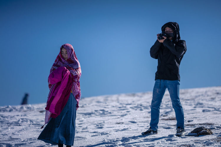 Blue Casual Clothing Clear Sky Day Digital Single-lens Reflex Camera Leisure Activity Lifestyles Nature Outdoors Photographing Photography Themes Real People Sky Standing Two People Young Adult Young Women Shades Of Winter Press For Progress