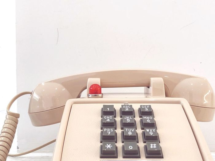 High angle view of telephone booth on table against white wall