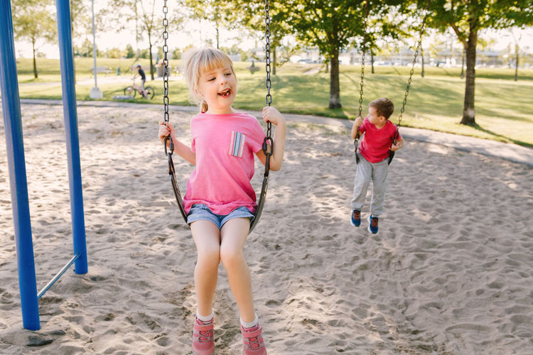 Siblings swinging at park