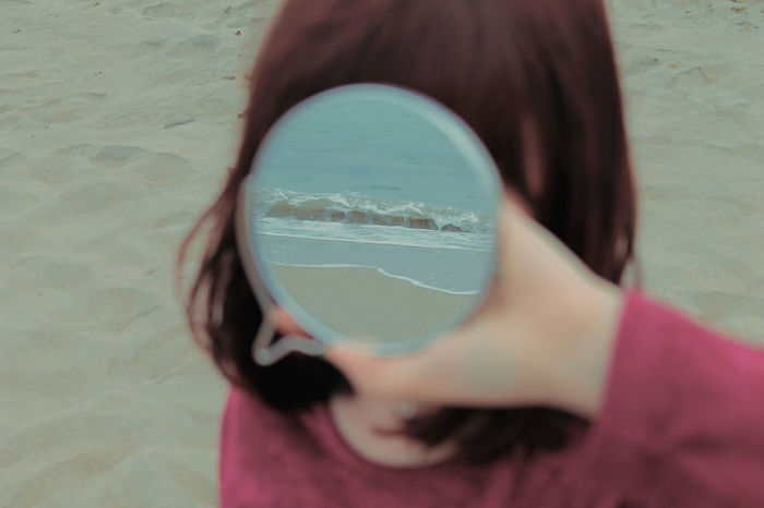 Close-up girl holding mirror with reflection of sea at beach