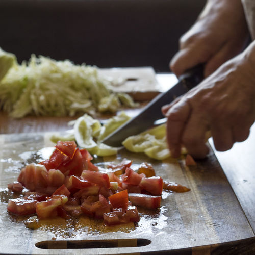 Human hand slicing vegetables