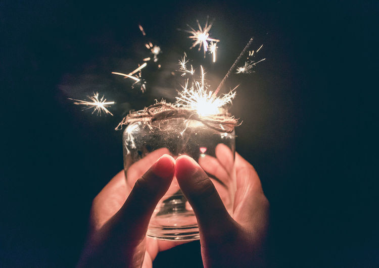 Cropped hands of person holding illuminated sparkler in jar at night