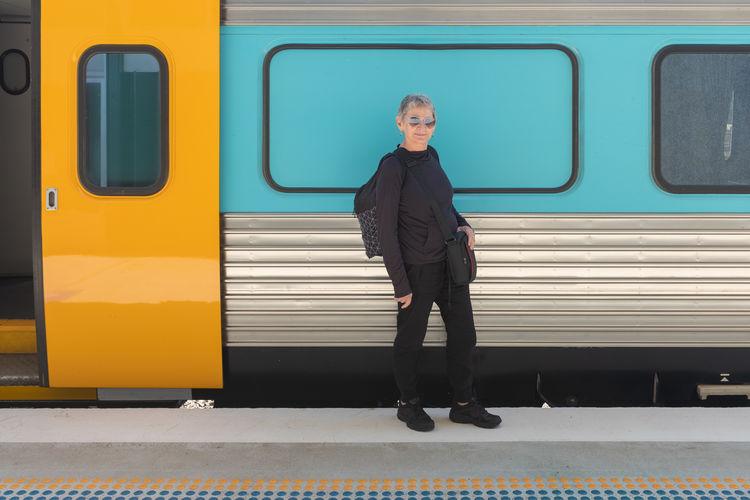 Full length portrait of senior woman standing against train at railroad station