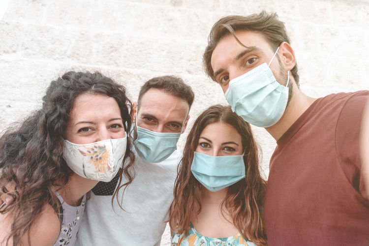 Portrait of smiling couple wearing flu mask standing against wall