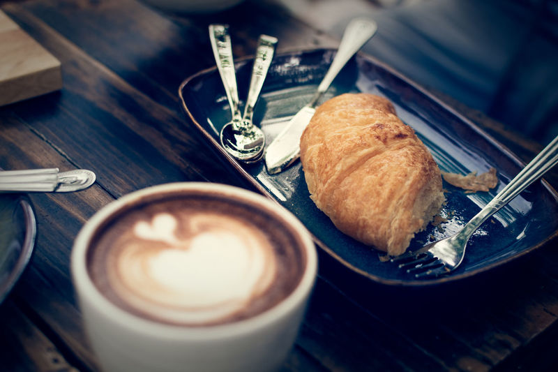 Croissant on wooden table with a cup of coffee, vintage color tone.