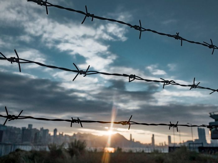 Low angle view of fence against sky during sunset