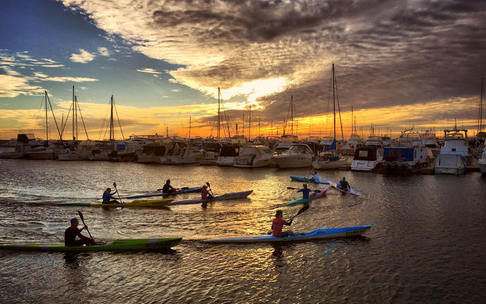 Sea kayakers gliding home at sunset. Beauty In Nature Boats And Moorings Boats And Water Golden Hour Harbourside Kayak Kayaking Kayaking In Nature Marina Nature Sea Sea Kayak Sea Kayaking Serene Serenity Sunset Sunset Silhouettes Tranquil Scene Yachts At Port