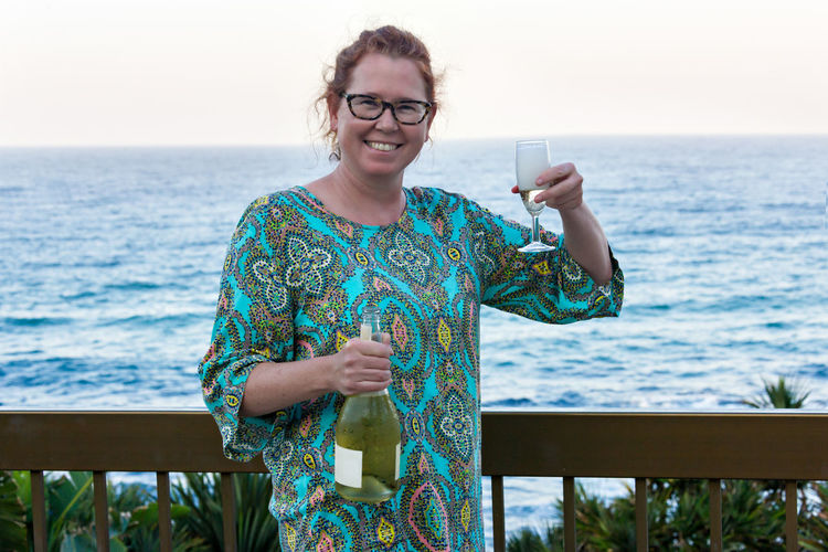 Portrait Of Smiling Mature Woman Holding Champagne Flute Against Sea