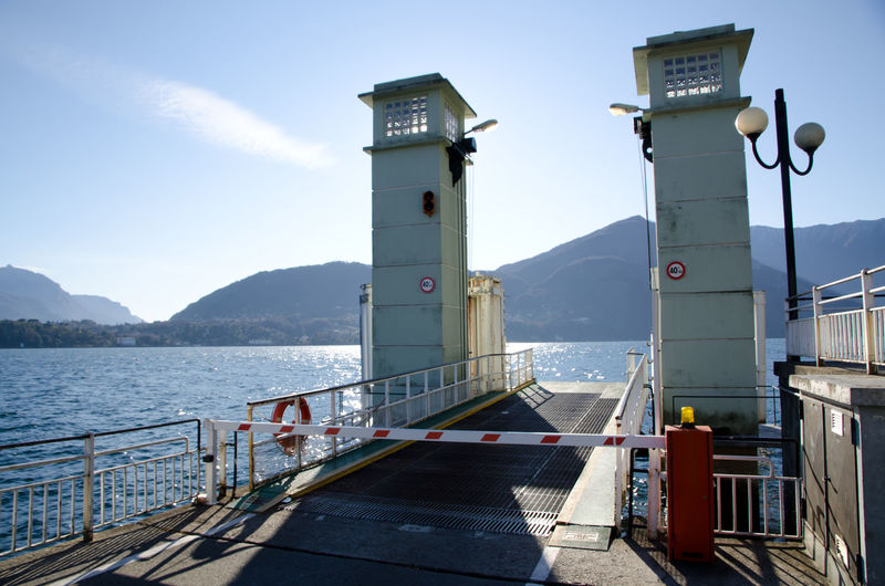 Ferry Terminal on Lake Como, Italy. Harbor Architecture Building Exterior Built Structure Day Ferry Terminal Guidance Mode Of Transportation Mountain Nature Nautical Vessel No People Outdoors Port Railing Safety Sea Sky Sunlight Tower Transportation Water