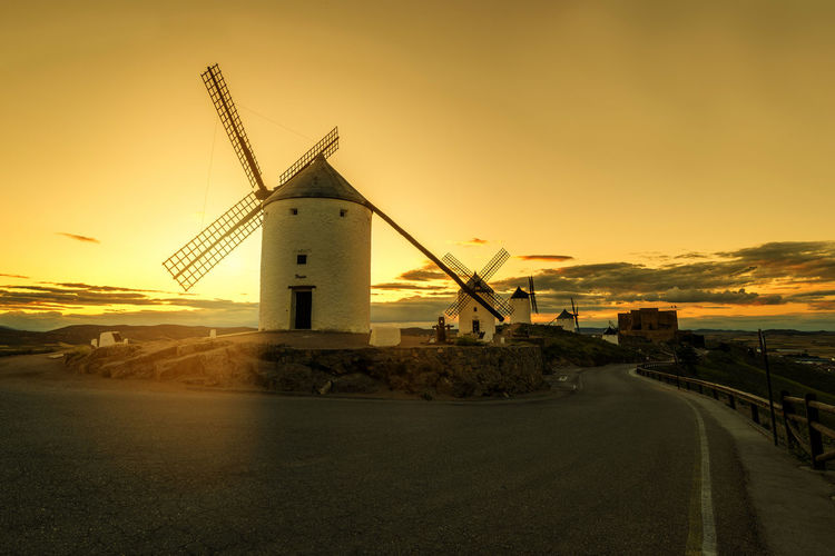 Quixote Windmill Architecture Beauty In Nature Building Exterior Built Structure Cloud - Sky Direction Environmental Conservation Fuel And Power Generation Nature No People Orange Color Outdoors Road Sky Sunset Toledo Transportation Turbine Water Wind Turbine