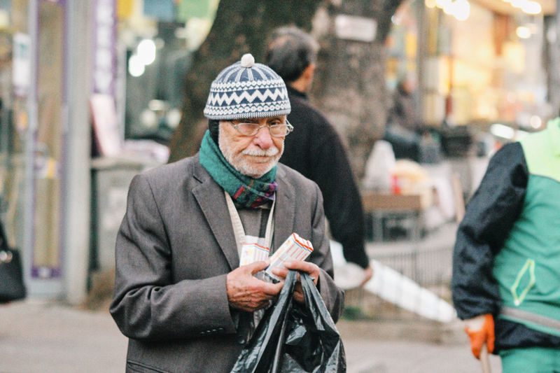 Portrait of man holding umbrella on street in city