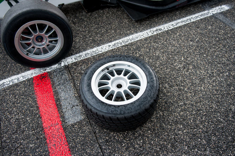 High Angle View Of Tire By Racecar On Motor Racing Track