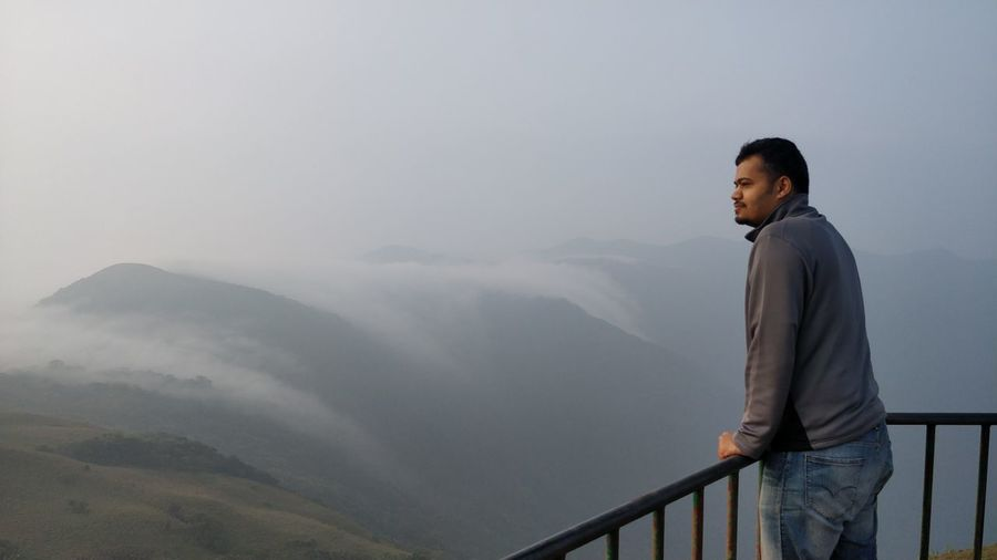 Man at observation point overlooking landscape during foggy weather