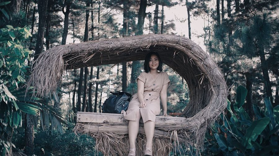 Portrait of young woman sitting under hay shelter in forest