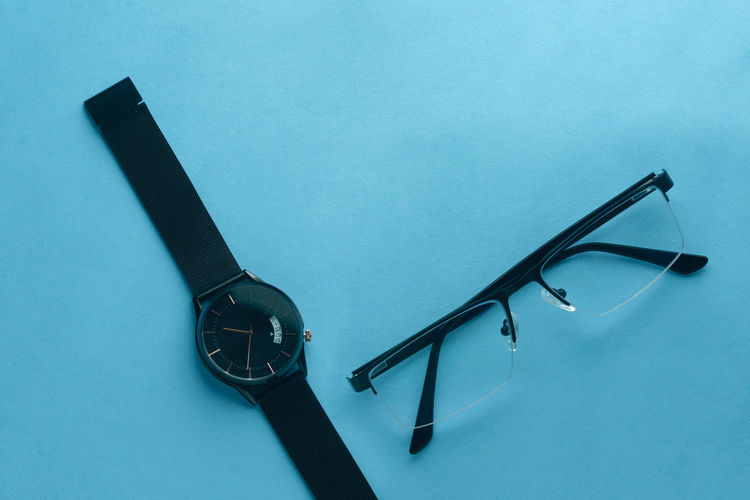 High angle view of eyeglasses on table against blue background