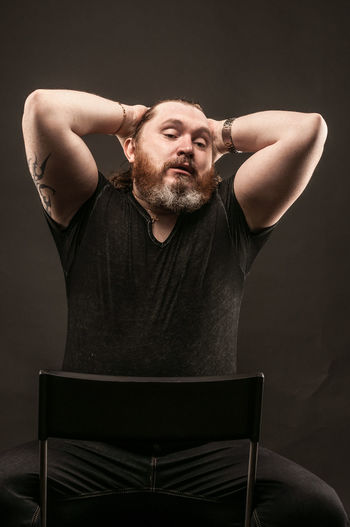 Bearded Man Sitting On Chair Against Black Background