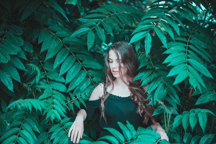 Smiling young woman standing amidst plants