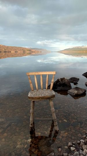 Take a seat...the view is lovely Loch Rannoch Reflections In The Water Evening Light Ethereal Scotland Scottish Highlands Take A Seat Water City Sea Beach Sunset Pastel Colored Relaxation Chair Arts Culture And Entertainment Sky Atmospheric Mood Romantic Sky Moody Sky Dramatic Landscape Atmosphere Postcard Calm Cloudscape Dramatic Sky