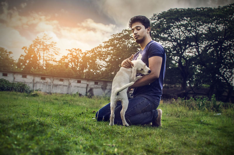 Side view of man stroking dog while kneeling on field against sky