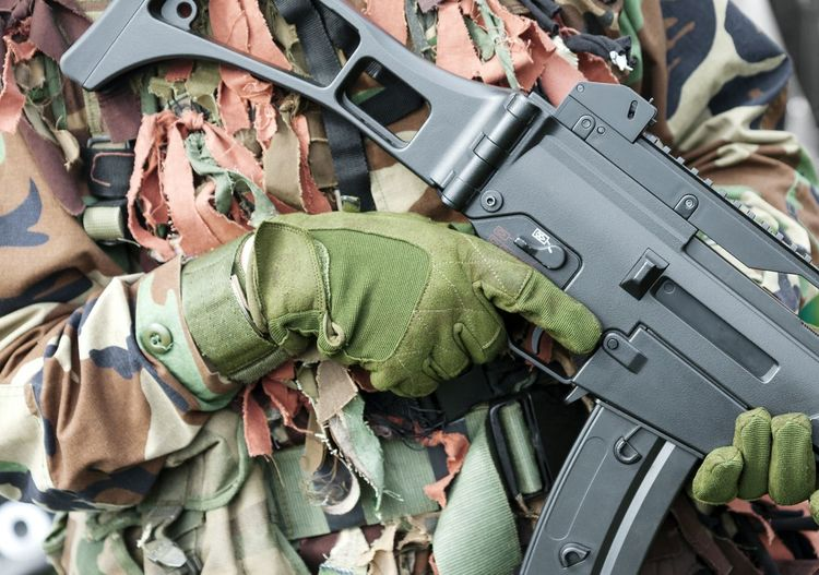 Midsection of army soldier holding rifle