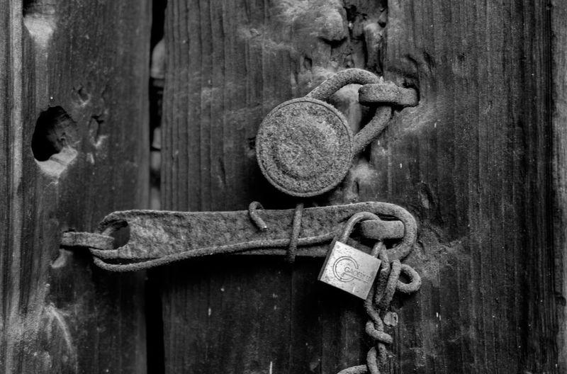 Close-up of padlock on rusty door