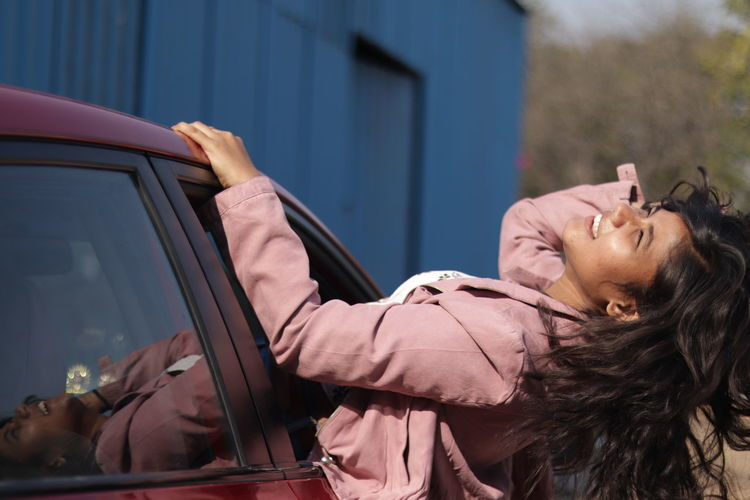 Side view of carefree woman leaning out from car window