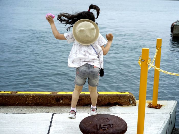 Rear view of girl jumping at harbor by sea