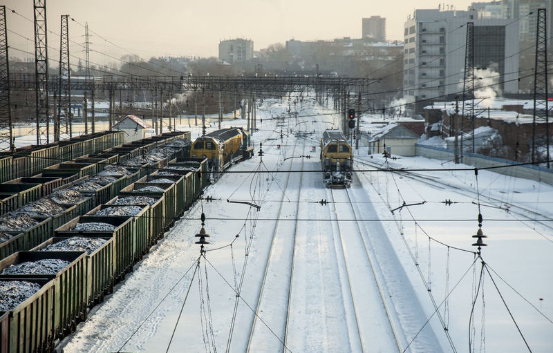 High angle view of trains moving on snow covered tracks against sky