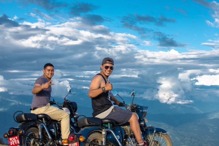 Friends riding motorcycle against blue sky