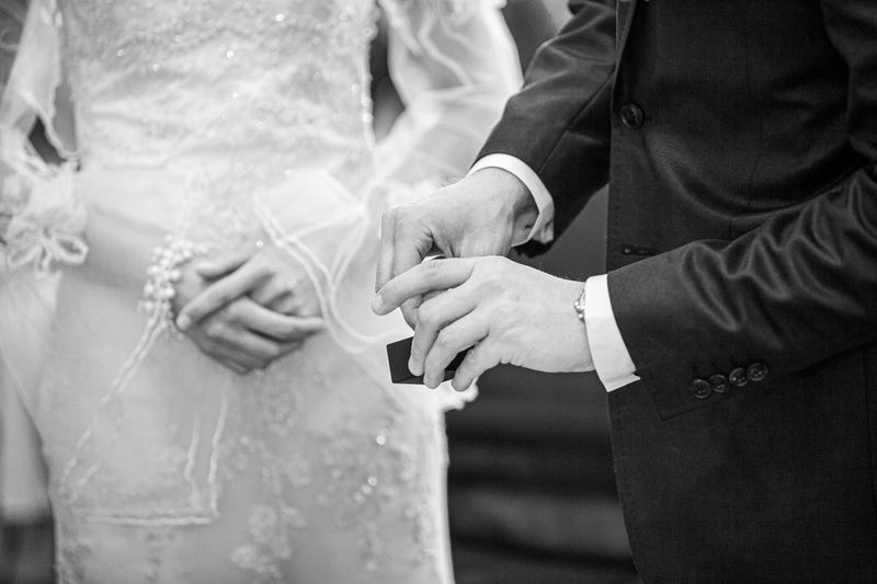 Midsection of couple exchanging ring