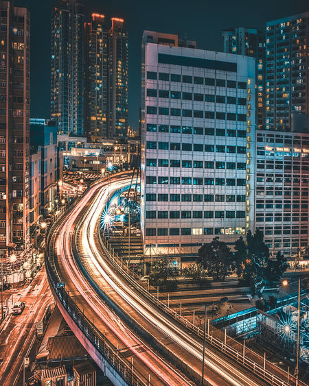 High angle view of light trails on street amidst buildings in city at night