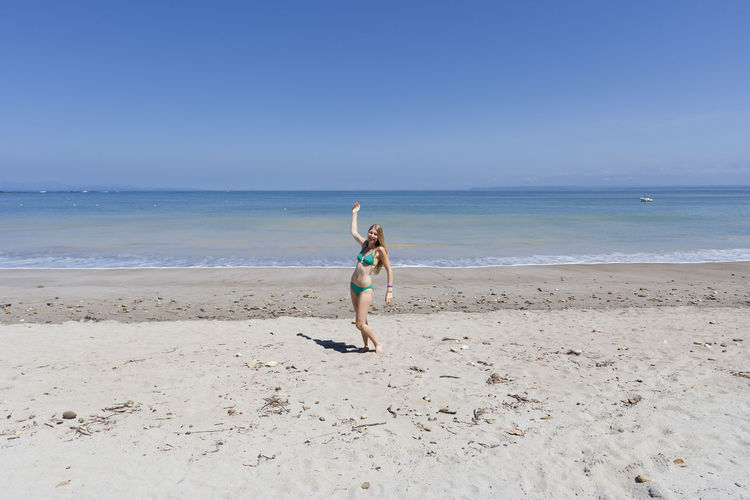 Full length of young woman in bikini gesturing at beach on sunny day