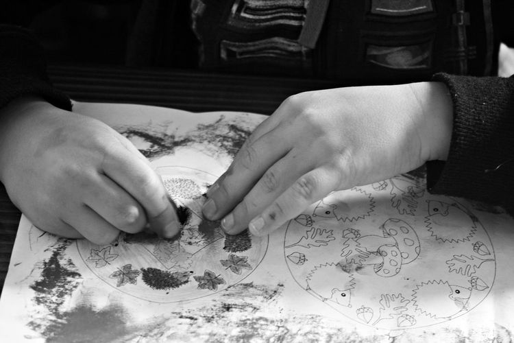 Cropped hands of child painting in paper