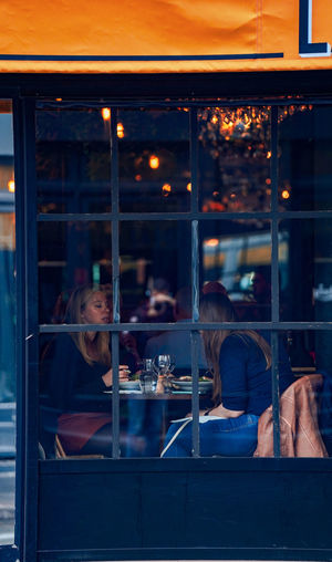 Reflection of people on glass window at restaurant