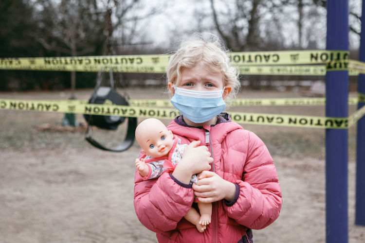 Portrait of cute girl wearing mask holding doll while standing park