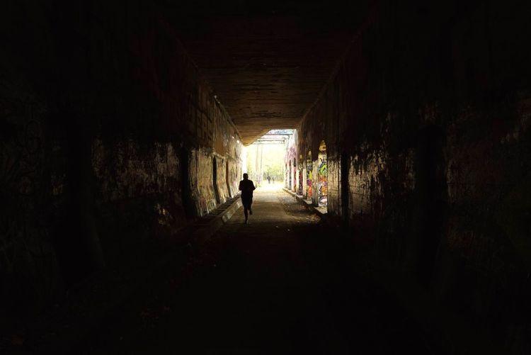 Full length of woman walking in tunnel