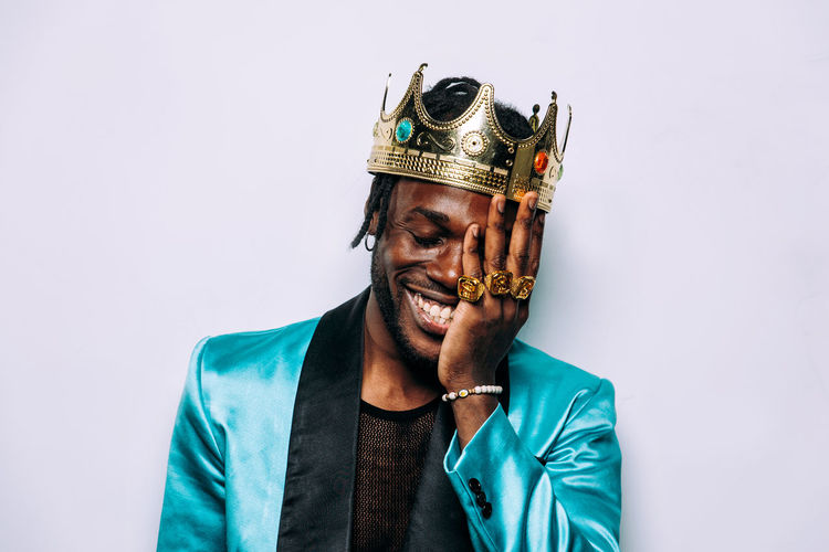 Smiling man wearing crown against white background