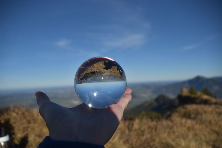 Person holding crystal ball against sky