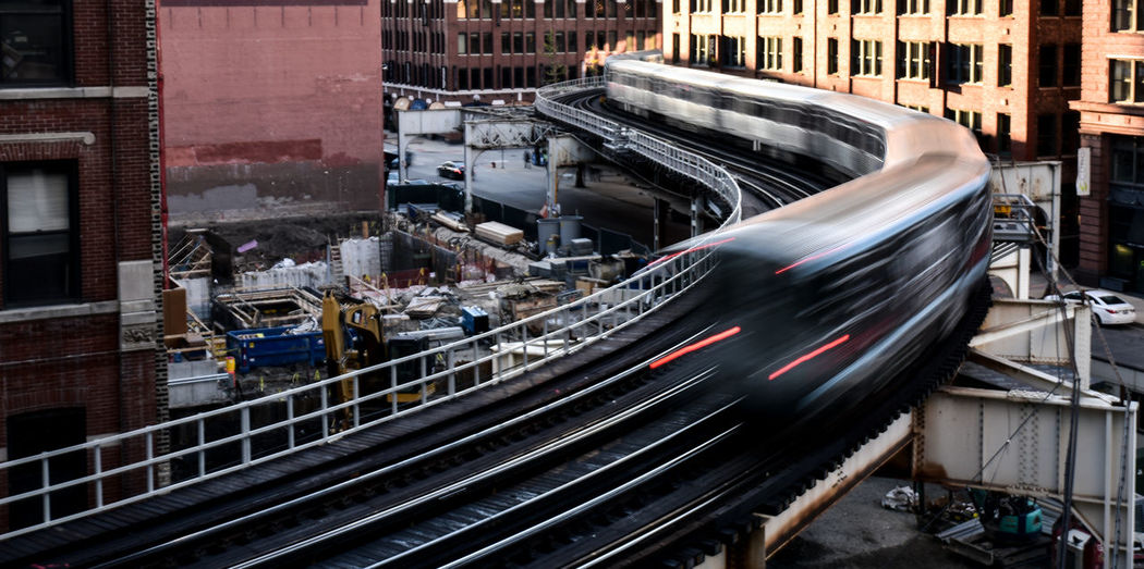 Blurred motion of train on railway bridge amidst buildings in city