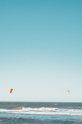 Scenic view of kitesurfers on sea against clear sky
