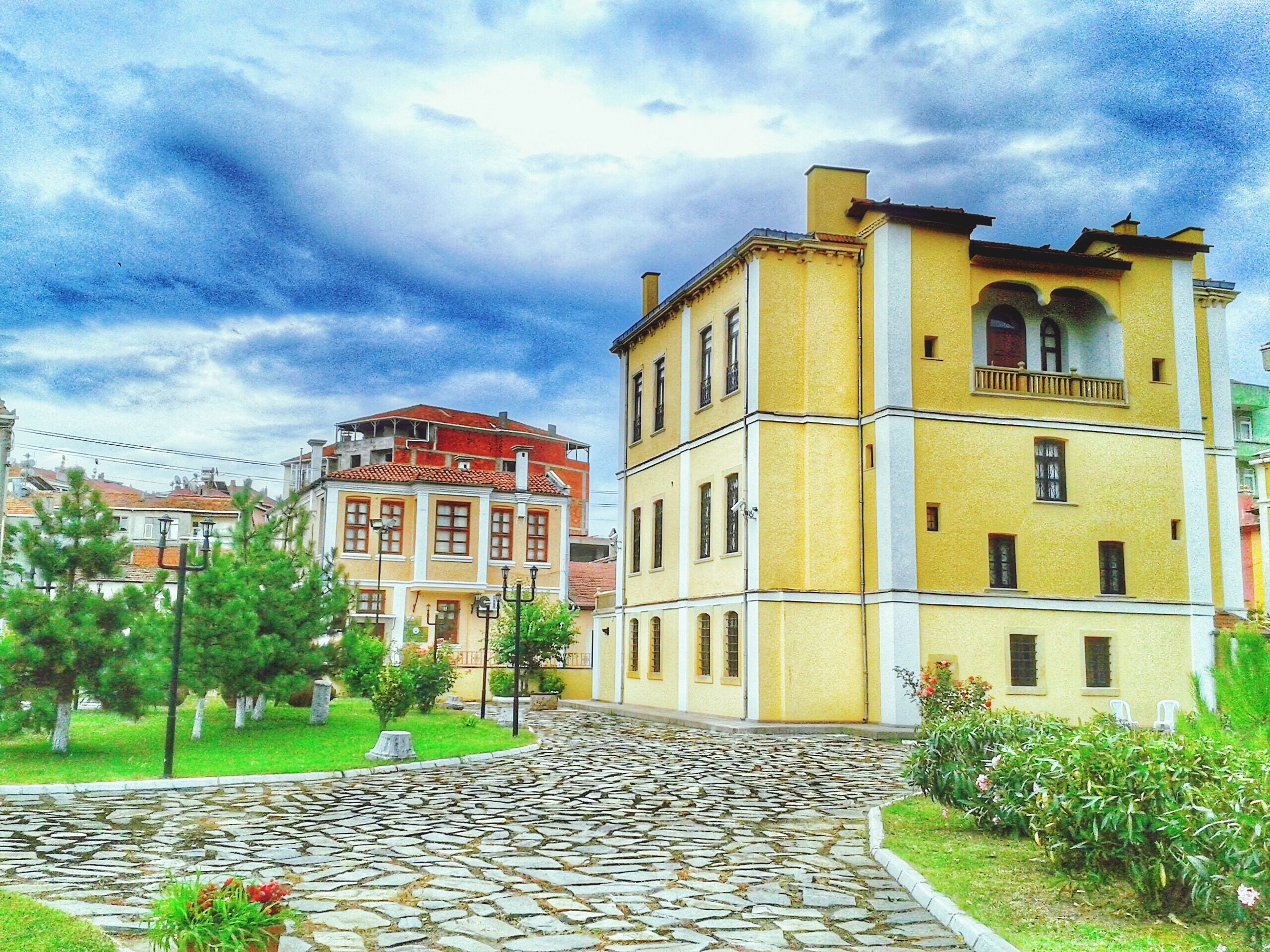 architecture, building exterior, built structure, sky, cloud - sky, cloudy, the way forward, house, residential structure, residential building, cloud, street, cobblestone, walkway, footpath, building, facade, window, pathway, day